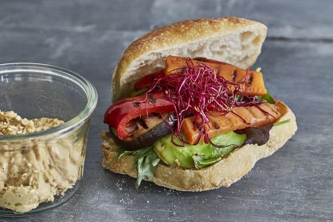 Veggiesandwichstykke med hummus, spirer og bagte grøntsager